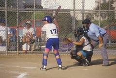 Ragazza che prepara al pipistrello con l'arbitro, gioco di softball delle ragazze, Brentwood, CA Fotografia Stock