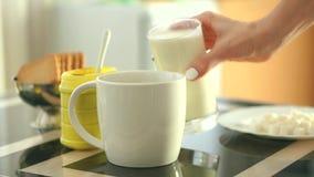 Ragazza che prepara la bevanda del cioccolato con latte e le caramelle gommosa e molle stock footage