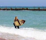 Ragazza che prepara per praticare il surfing Immagini Stock Libere da Diritti