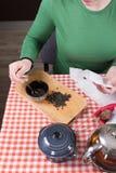 Ragazza che produce tè in cucina Immagine Stock