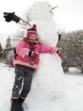 Ragazza che propone con il suo grande pupazzo di neve. Fotografia Stock Libera da Diritti