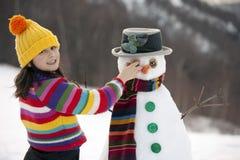Ragazza che propone con il suo pupazzo di neve Fotografie Stock