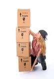 Ragazza che prova ad alzare una pila di scatole di cartone Immagine Stock Libera da Diritti