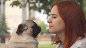 Ragazza che prova a baciare il suo carlino e che esamina macchina fotografica archivi video