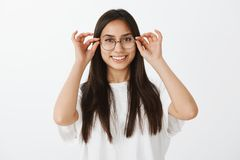 Ragazza che prova i nuovi vetri al deposito dell'ottico Ritratto di bello cliente femminile soddisfatto, mettente su alla moda Fotografia Stock Libera da Diritti