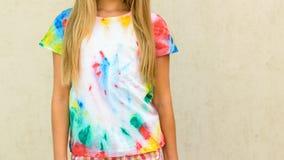 Ragazza che prova su una maglietta dipinta nello stile della tintura del legame Fotografia Stock