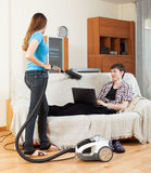 Ragazza che pulisce a casa mentre uomo con il computer portatile Fotografia Stock Libera da Diritti