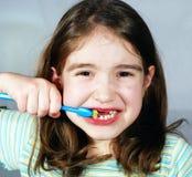 Ragazza che pulisce i suoi denti Fotografie Stock