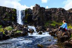 Ragazza che raffredda vicino alla cascata in Islanda Immagine Stock Libera da Diritti