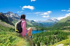 Ragazza che riposa durante il viaggio nelle montagne che guardano la vista OV Immagini Stock
