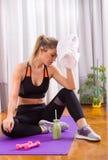 Ragazza che riposa sul pavimento dopo l'allenamento Immagini Stock