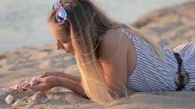Ragazza che riposa sulla sabbia vicino al fiume nella sera stock footage