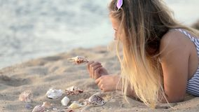 Ragazza che riposa sulla sabbia vicino al fiume nella sera archivi video