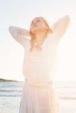 Ragazza che riposa sulla spiaggia alla luce solare Fotografia Stock