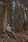 Ragazza che riposa sulle radici dell'albero, nel vicolo della foresta Immagine Stock Libera da Diritti