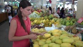 Ragazza che sceglie frutta fresca nel mercato Alto vicino del mango video d archivio