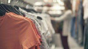 Ragazza che sceglie i vestiti della maglietta, backgound vago Fuoco selettivo Immagini Stock