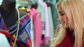 Ragazza che sceglie i vestiti in un deposito, esamina il cappotto sul manichino archivi video