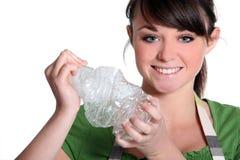 Ragazza che schiaccia bottiglia di plastica Fotografie Stock Libere da Diritti