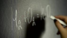 Ragazza che scrive formula di chimica sul bordo nero stock footage