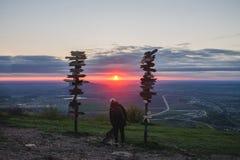 Ragazza che segna cane sopra la montagna che esamina il tramonto e la pianura, accanto ai segni di legno delle città Immagini Stock Libere da Diritti