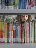 Ragazza che seleziona i libri a partire dallo scaffale per libri delle biblioteche Immagini Stock Libere da Diritti