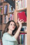 Ragazza che seleziona un libro dalla biblioteca Immagine Stock