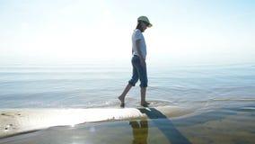 Ragazza che si allontana lungo la spiaggia sabbiosa dorata pulita video d archivio