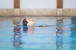 Ragazza che si distende nella piscina Immagini Stock