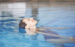 Ragazza che si distende nella piscina Fotografia Stock