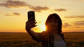 Ragazza che si fa su un bello tramonto contro un fondo del giacimento di grano archivi video