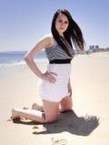Ragazza che si inginocchia sulla sabbia Fotografia Stock