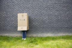 Ragazza che si leva in piedi contro una parete Fotografia Stock