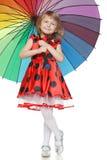 Ragazza che si leva in piedi sotto l'ombrello variopinto Fotografie Stock