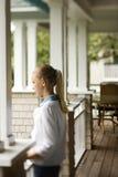 Ragazza che si leva in piedi sul portico. Fotografie Stock