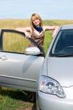 Ragazza che si leva in piedi vicino alla sua automobile Fotografie Stock Libere da Diritti