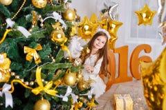 Ragazza che si nasconde dietro l'albero di Natale Nuovo anno 2016 Fotografie Stock