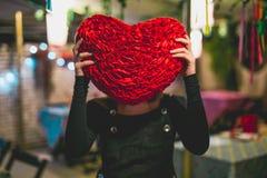 Ragazza che si nasconde dietro un cuscino del cuore immagini stock libere da diritti