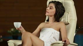 Ragazza che si rilassa nel salone della stazione termale e nel tè della bevanda stock footage