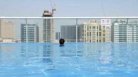 Ragazza che si rilassa nello stagno sul tetto con la vista urbana sul grattacielo video d archivio