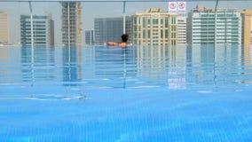 Ragazza che si rilassa nello stagno sul tetto con la vista urbana sul grattacielo archivi video