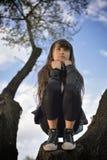 Ragazza che si rilassa su un albero Fotografie Stock