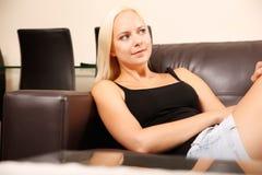 Ragazza che si rilassa su un sofà Fotografie Stock Libere da Diritti