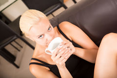 Ragazza che si rilassa su un sofà che beve una tazza di caffè Fotografie Stock