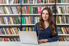 Ragazza che si siede ad uno scrittorio nella biblioteca che lavora con il suo rivestimento Immagini Stock Libere da Diritti