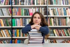 Ragazza che si siede ad uno scrittorio nella biblioteca con le sue armi su una b Fotografia Stock Libera da Diritti