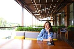 Ragazza che si siede al caffè con lo smartphone ed il taccuino sulla tavola Immagine Stock