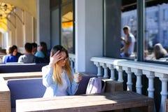 Ragazza che si siede al caffè della via ed al caffè bevente Fotografia Stock Libera da Diritti