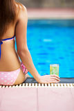 Ragazza che si siede al poolside con il vetro di birra Fotografia Stock Libera da Diritti