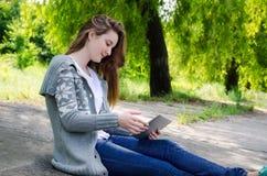 Ragazza che si siede all'aperto per mezzo di un ridurre in pani dello schermo attivabile al tatto Fotografie Stock Libere da Diritti